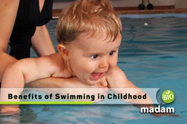 trainer teaching swimming to a baby because there are many benefits of swimming